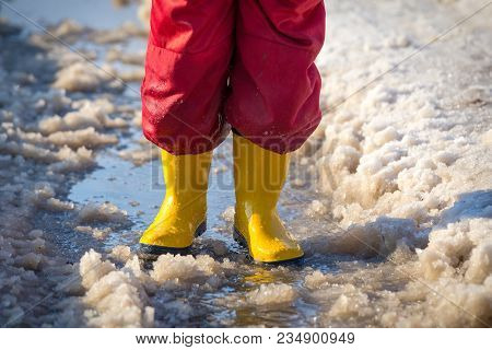 Kid Legs In Yellow Rainboots Standing In The Ice Puddle With Melting Snow At Sunny Spring Day, Outdo