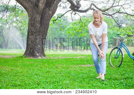 Senior Woman Walking In Autumn Park And Having Knee Pain. Arthritis Pain Concept.