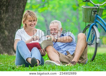 Happy Elderly Couple With Smiling Face Enjoying Together, Reading A Book With Magnifying Glass In Th