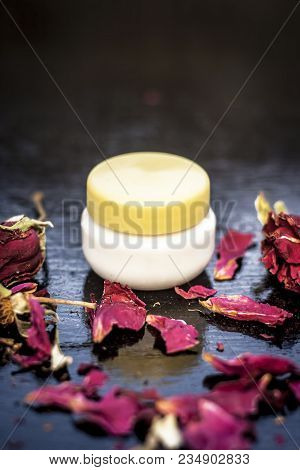 Close up of cream rose or gulab or rosa with fresh petals of rose on black wooden surface it is an antiseptic and it removes the dead skin and wrinkles. poster