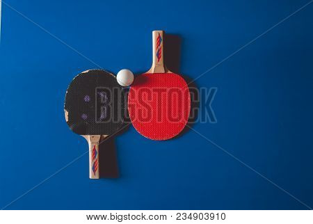Two Frayed Tennis Rackets On A Blue Tennis Table Background.