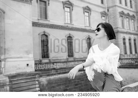 Model In Fashionable Clothes. Woman Sit On Stone Fence On House Facade. Beauty, Look, Style. Fashion