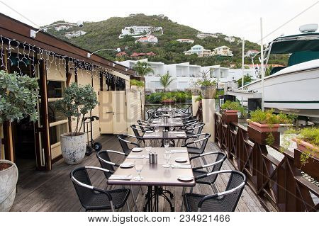 Restaurant Open Air In Philipsburg, Sint Maarten. Terrace With Tables, Chairs And Yacht In Sea. Eati