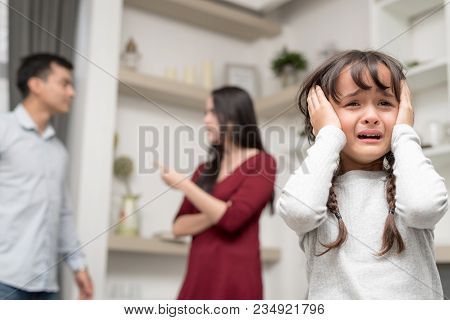 Domestic Violence And Family Conflict Concept. Sadness Little Girl Against Blured Of Mother Fighting