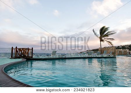 Pool With Sea View In Philipsburg, Sint Maarten. Swimming Pool With Blue Water Under Evening Sky. Be