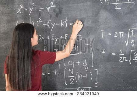Beautiful Young Girl Teacher Writing Physics Formulas On Blackboard.