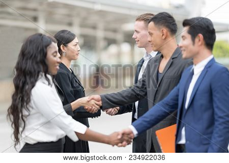 Business Partners Shaking Hand After Complete A Deal. Confident And Active Businesspersons Creative