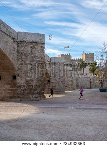Valencia, Spain - March 16, 2018: Jogger On Dry Riverbed In Old City Of Valencia On Coast Of Spain