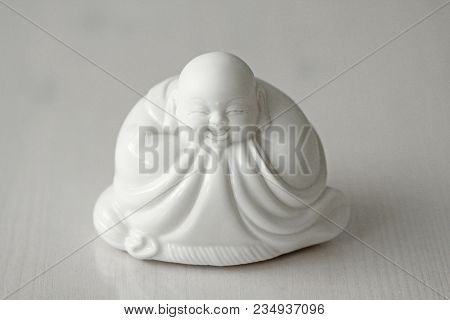 Buddha And Smile. Laughing Buddha. White Buddha Sits And Smiles On The White Background.
