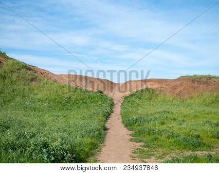 Path In Grassy Field Leading To A Dirt Hill On A Sunny Day