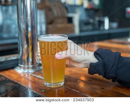 Woman Reaching For Full Pint Glass Of Ipa In A Bar In A Brewery