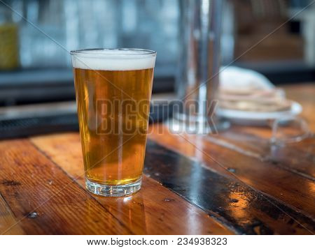 Full Pint Glass Of Beer Sitting On Bar Counter Ready To Be Drinked