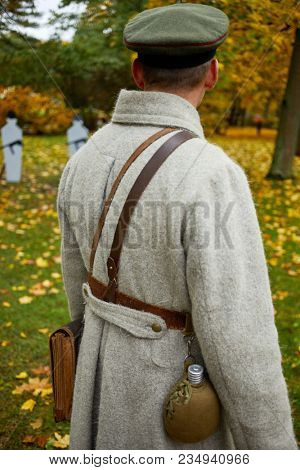 Man in military uniform looks at stationary targets in autumn park, rear view.