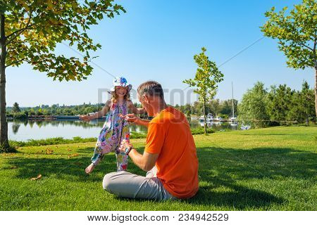 Happy Father With A Small Daughter Are Playing On A Green Meadow