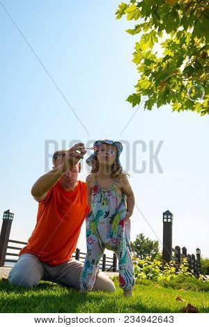 Enthusiastic Father With A Small Daughter On A Green Meadow