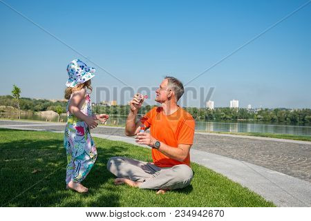 Happy Father With A Small Daughter Are Playing River In A Park