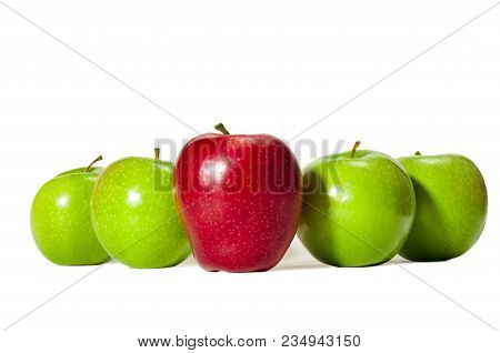 Horizontal Straight On Shot Of One Red Delicious Apple Standing In Front Of Four Green Granny Smith