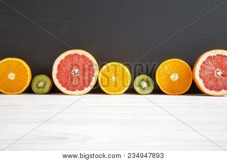 Sliced Kiwi, Orange, Grapefruit And Mandarin On Black And White Wooden Background. Copy Space. Summe