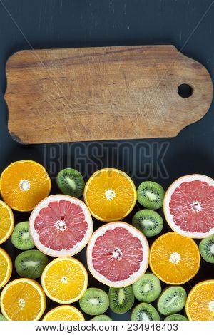 Flat Lay. Top View. Board With Sliced Colorful  Fresh Fruits: Kiwi, Orange, Grapefruit And Mandarin