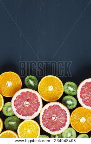 Flat Lay. Top View. Sliced Colorful  Fresh Fruits: Kiwi, Orange, Grapefruit And Mandarin On Black Ba