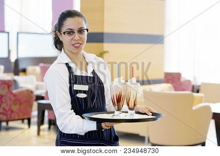 The Waitress Bears Two Vanilla Milkshakes For The Client Of The Hotel Restaurant. Two Chocolate Dair