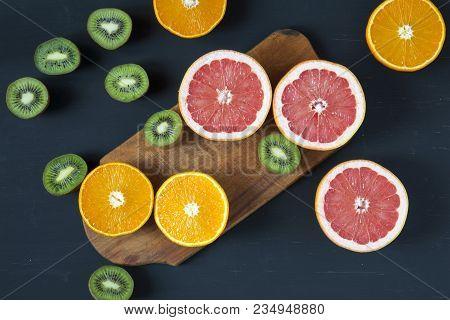 Flat Lay. Top View. Sliced Colorful  Fresh Fruits: Kiwi, Orange, Grapefruit And Mandarin On Wooden B