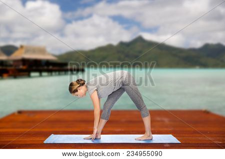 fitness, sport, people and healthy lifestyle concept - woman making yoga intense stretch pose on wooden pier over island beach and bungalow background