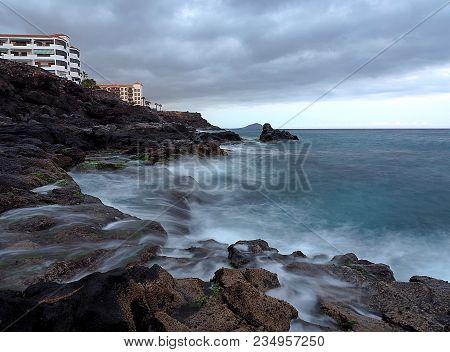 The Shore Of The Ocean. Costa Del Siencio, Tenetyfa, Spain - March 24, 2018 Blurry Waves Of The Atla