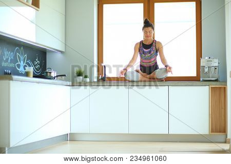 Young beautiful woman sitting at the kitchen table in the lotus position. Woman. Yoga