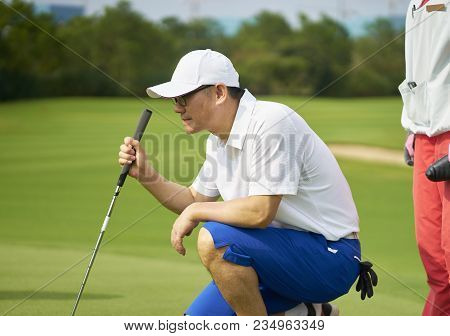Asian Golfer Crouching In Golf Course Aiming And Preparing For Putting