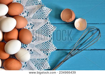A Top View Image Of Farm Fresh Organic Eggs With Wire Whisk On An Old Blue Coutry Style Kitchen Tabl