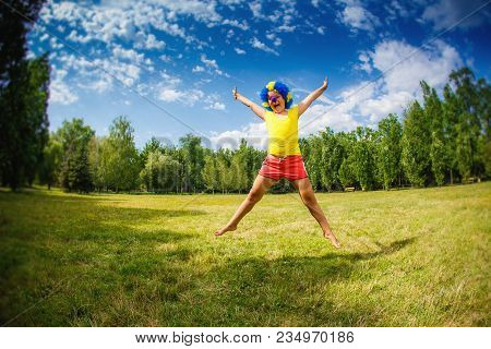 Child Kid Girl With Party Clown Blue Wig Funny Happy Open Arms Expression And Garlands Is Jumping In