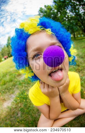 Funny Girl In Clown Wig With Red Nose Puts Out The Tongue