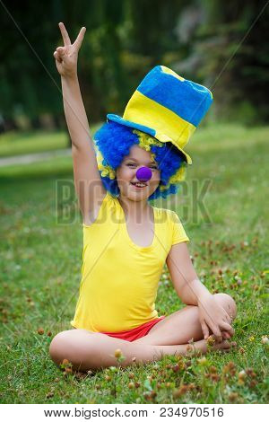 Girl Is Sitting On The Grass In Clown Wig And Hat