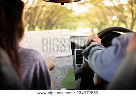 Asian Man And Woman Using Map On Road Trip And Happy Young Couple With A Map In The Car. Blurred And