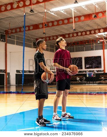 Teenage boys holding basketball on the court team and aspiration concept