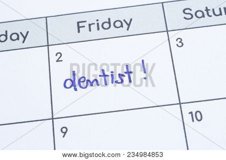 Closeup On Calendar Page, Focus On Blue Handwriting The Word dentist Written On Timetable Date 2nd U
