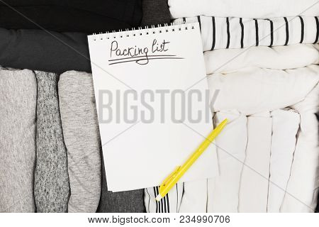 Packing Of Monochrome Clothes In Black Suitcase. Packing List In White Notebook. Top View, Copy Spac
