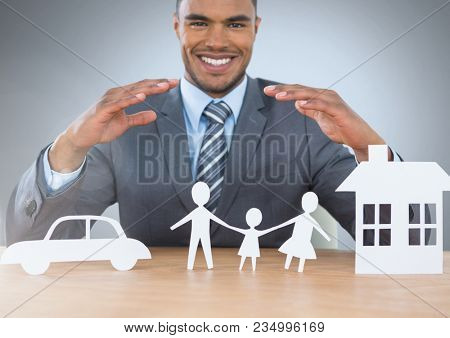 Man with cut outs of home insurance car and family