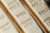 Pure 999.9 shiny fine gold bullions ingot bars, closed up macro shot as financial asset, investment and wealth concept. poster