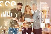 Looking calm. Clever experienced eco engineer holding a miniature windmill turbine and his smart young colleague standing near with a modern tablet in her hands poster