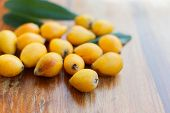 a bunch of ripe fruit medlar on a brown wooden background poster