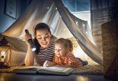 Family bedtime. Mom and child daughter are reading a book in tent. Pretty young mother and lovely girl having fun in children room. poster