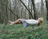 Beautiful girl hovering above the ground enjoying in levitation in forest.  poster
