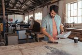 Skilled young artisan standing at a workbench in his woodworking studio using a digital tablet and reading a notebook of designs poster