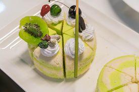 Pistachio Cake Sliced On White Wooden Background.