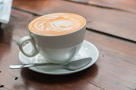 A Cup Of Coffee With Latte Art In Hearth Shape In White Coffee Cup On Wooden Table Background.
