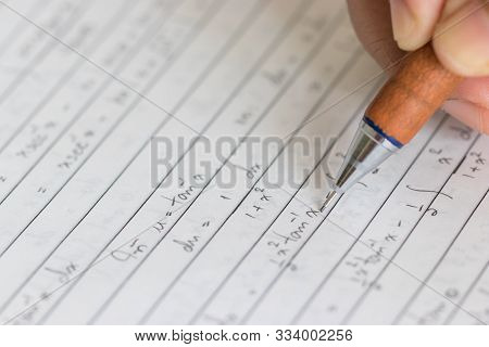 Close-up Senior Hand Is Holding Pencil For Compute The Physics And Maths Problem Using Mathematics K