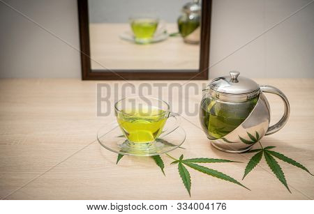 A Glass Of Hot Marijuana Tea And Tea Pot On The Table . Cannabis Concept.