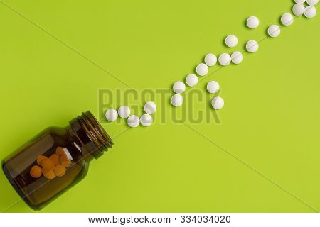 The White Pills Are Scattered On A Green Background. Glass Medicinal Bottle.